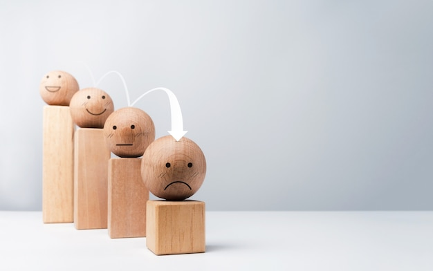 La satisfaction, l'échec de l'entreprise, la crise financière, le concept de crash d'effondrement de problème économique. l'émoticône, l'émotion fait face à des boules en bois et des blocs de cubes en bois des étapes du graphique avec la flèche vers le bas sur fond blanc.