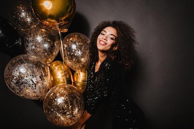 Satisfait de belle femme tenant des ballons dorés