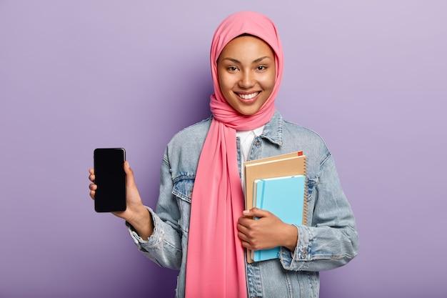 Satisfait de charmante jeune femme musulmane en hijab rose sur la tête