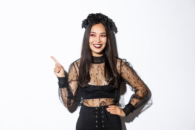 Satisfait femme asiatique souriante en costume de sorcière maléfique ou banshee célébrant halloween, à la recherche de plaisir et pointant le doigt dans le coin supérieur gauche, montrant votre bannière promotionnelle, fond blanc.