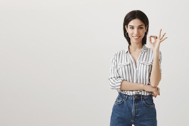 Satisfait femme brune attrayante montrant un geste correct, garantir la qualité du produit
