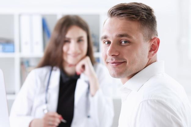 Satisfait heureux beau patient masculin souriant avec le médecin