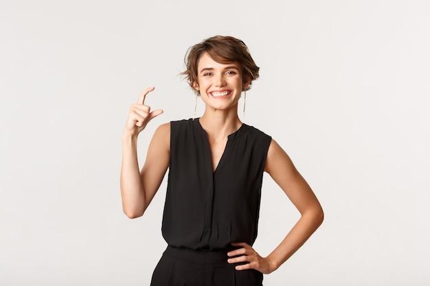 Satisfait et heureux jeune femme souriant tout en montrant quelque chose de petit, petit ou minuscule, debout blanc.