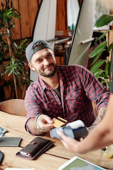 Satisfait de l'hôte beau en casquette de balle payant pour le dîner avec carte sans fil dans un café moderne