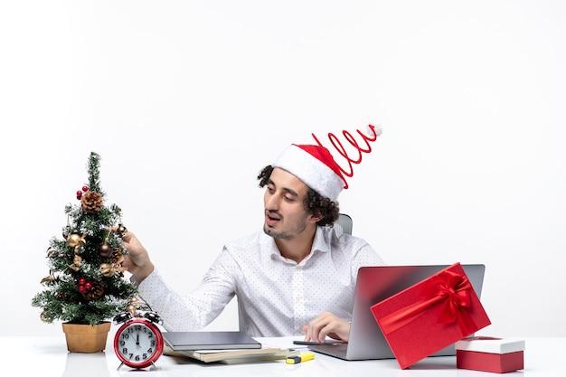 Satisfait de jeune homme d'affaires avec drôle de chapeau de père noël décorant l'arbre de noël et célébrant noël au bureau sur fond blanc