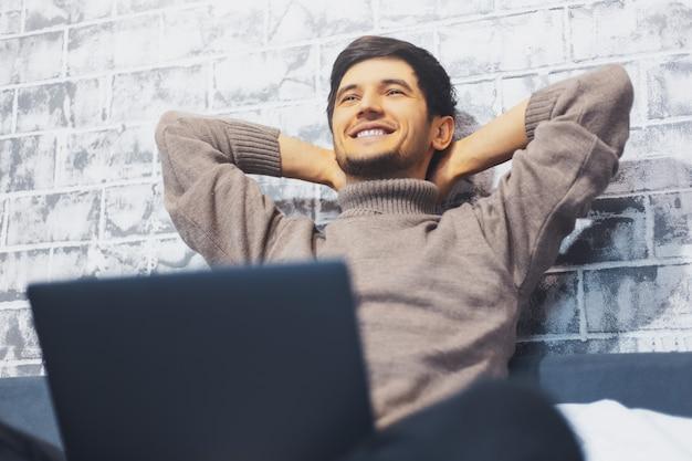 Satisfait jeune homme avec ordinateur portable sur le lit sur le mur du mur de briques.