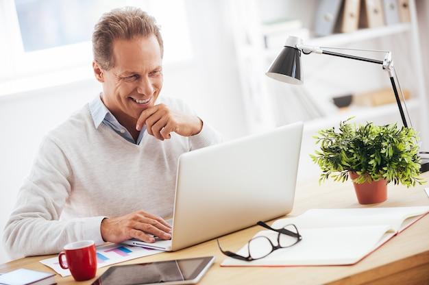 Satisfait de son travail. homme mûr gai travaillant sur l'ordinateur portable et souriant alors qu'il était assis sur son lieu de travail