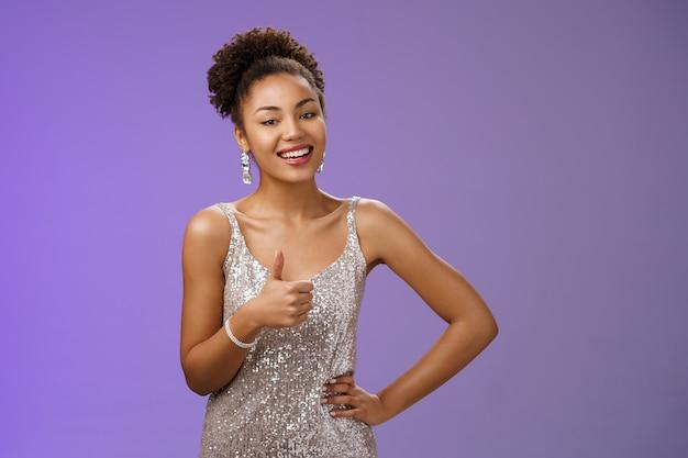 Satisfaite, charmante, charmante, femme afro-américaine, souriante avec plaisir, montrant le pouce vers le haut, ravie comme une grande maquilleuse, debout, ravie, approuvant, recommandant un bon travail, fond bleu.