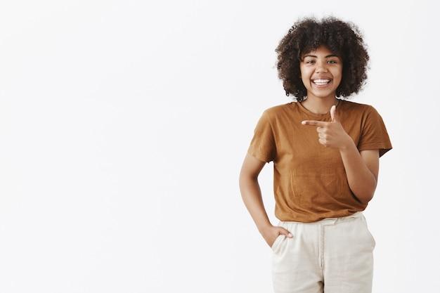 Satsified heureux femme afro-américaine en t-shirt et pantalon élégant marron tenant la main dans la poche souriant joyeusement tout en pointant vers la gauche donnant des conseils où aller ou dans quel sens choisir sur mur gris