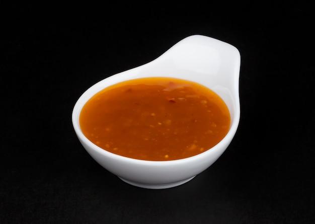 Sauce aigre douce dans un bol blanc isolé sur fond noir