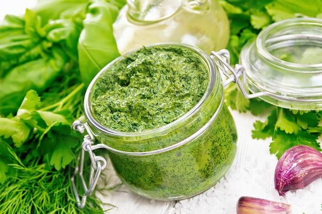 Sauce à l'aneth, persil, basilic, coriandre, autres herbes épicées, ail et huile végétale dans un bocal en verre, gros sel sur fond de planche de bois blanc