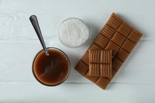 Sauce au caramel, bar et sel sur fond de bois blanc