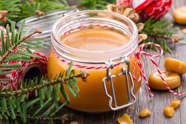 Sauce au caramel salé maison dans un bocal en verre et décor de noël sur bois