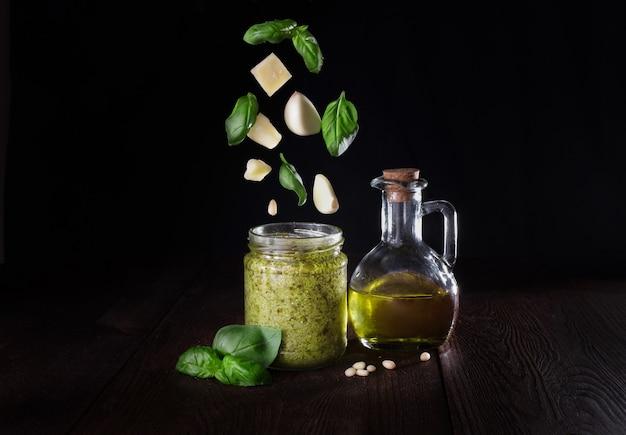 Sauce au pesto dans un bocal en verre avec des ingrédients volants.