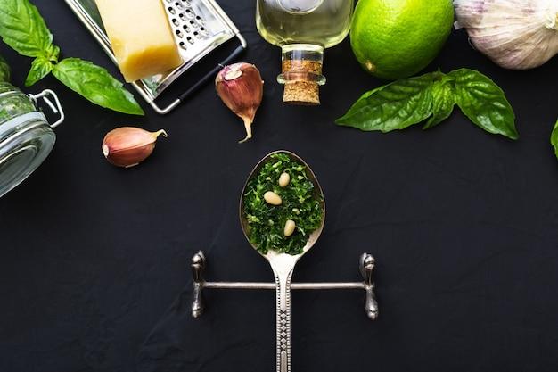 Sauce au pesto dans une cuillère vintage avec ingrédients pignons de pin, basilic vert, ail, parmesan, huile d'olive sur fond de ciment noir foncé.