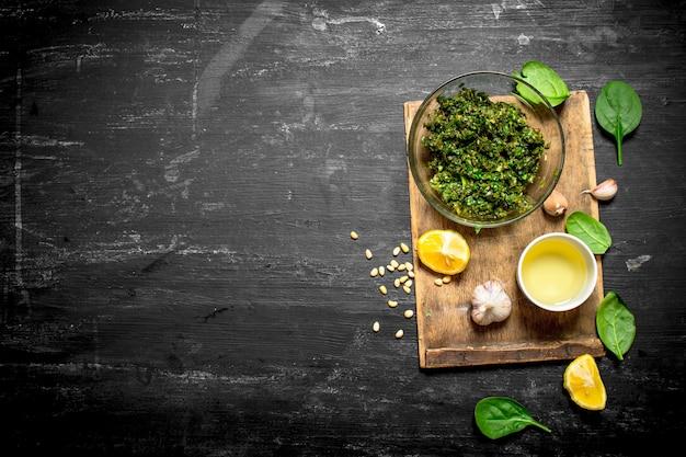 Sauce au pesto avec de l'huile d'olive, de l'ail et d'autres ingrédients sur la table en bois noire.