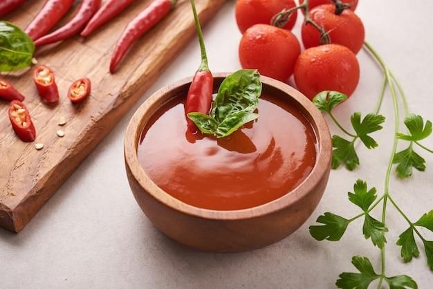 Sauce au piment rouge. ketchup aux tomates, sauce chili, purée de piment, tomates et ail. sur une planche à découper en bois sur une surface en pierre. vue de dessus.