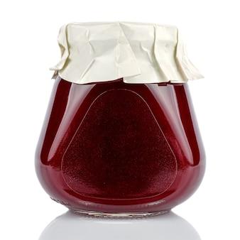 Sauce aux canneberges dans un bocal en verre conique fermé avec un couvercle enveloppé dans du papier blanc isolé sur fond blanc