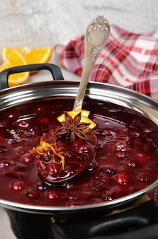 Sauce aux canneberges fraîchement cuite avec zeste d'orange et tranches d'agrumes dans une casserole