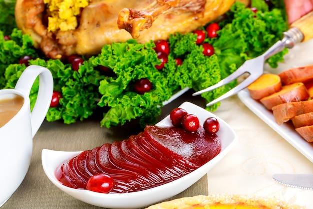 Sauce aux canneberges sur table de fête avec dinde pour le jour de thanksgiving.