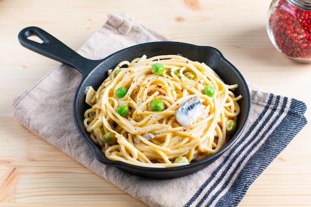 Sauce blanche crémeuse spaghetti concept alimentaire dans une poêle en fonte sur fond de bois