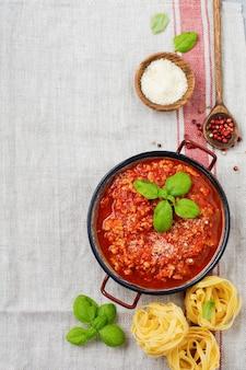 Sauce bolognaise italienne traditionnelle dans une casserole un vieux fond en bois foncé