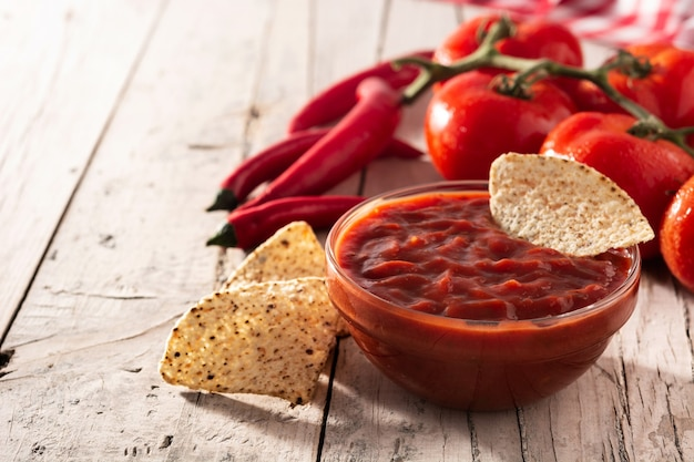 Sauce chili épicée dans un bol avec des chips de nacho sur table en bois