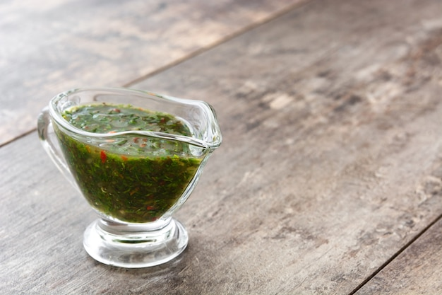 Sauce chimichurri verte sur l'espace de copie de table en bois