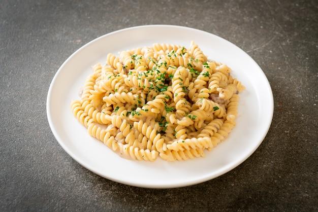 Sauce crémeuse aux champignons et pâtes spirales ou spirales avec persil - cuisine italienne