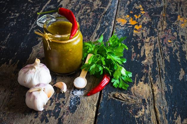 Sauce géorgienne traditionnelle tkemali avec des ingrédients sur fond en bois
