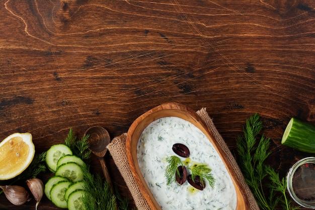 Sauce grecque traditionnelle tzatziki dans un bol en bois d'olive sur l'ancienne surface rustique