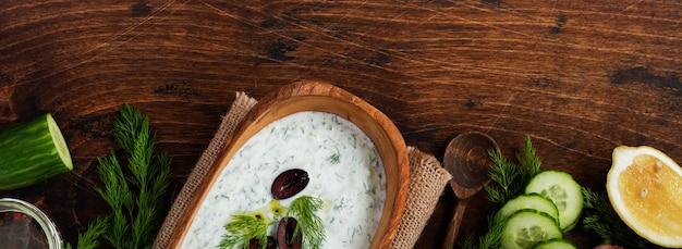 Sauce grecque traditionnelle tzatziki dans un bol en bois d'olive sur fond rustique ancien. vue de dessus.