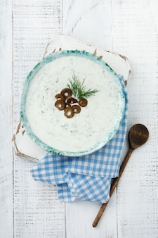 Sauce grecque traditionnelle tzatziki. yaourt, concombre, aneth, ail et huile de sel dans un bol en céramique sur un fond en bois clair.
