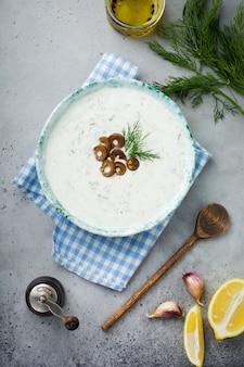 Sauce grecque traditionnelle tzatziki. yaourt, concombre, aneth, ail et huile de sel dans un bol en céramique sur une pierre grise ou une surface en béton. style rustique. mise au point sélective.
