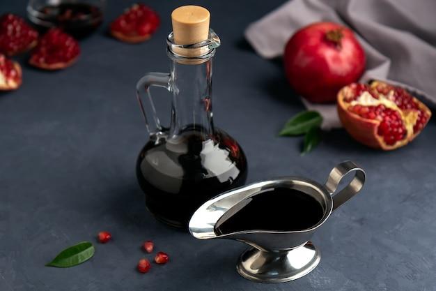 Sauce à la grenade dans une bouteille et une saucière avec des grains et des morceaux de grenade sur dark