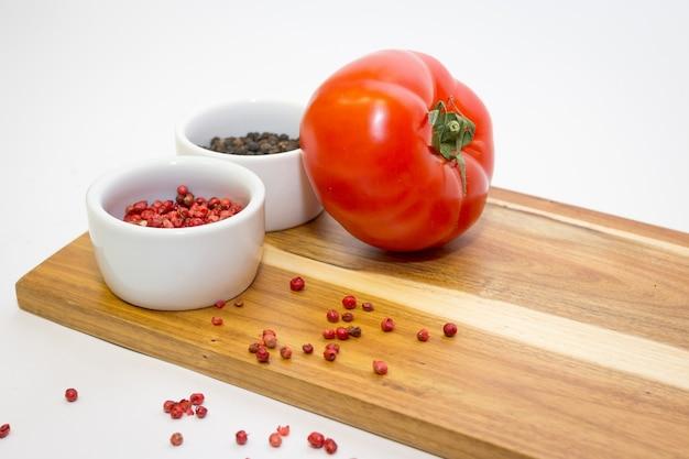 Sauce ketchup aux tomates. tomate rouge mûre fraîche et piments rouges dans un pot en céramique blanc sur fond blanc. poivre rouge et noir. arrière-plan de cuisson avec des épices, espace .copy