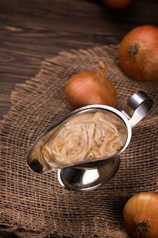 Sauce à l'oignon sur une table en bois. style vintage