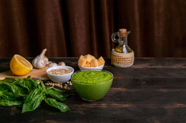 Sauce pesto dans un bol en verre et ingrédients pour faire de la sauce au basilic à la maison sur fond de bois avec espace de copie