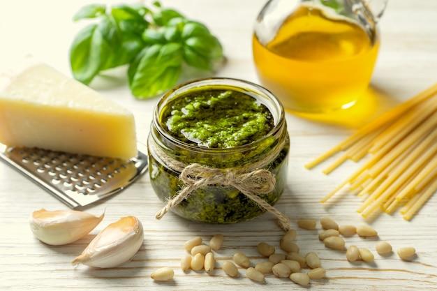 Sauce pesto maison avec des ingrédients. sauce pesto dans un bol blanc avec basilic, huile d'olive, pignons, pâtes et parmesan sur fond de bois blanc