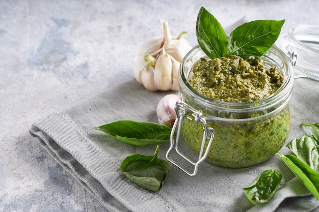 Sauce pesto traditionnelle au basilic italien dans un bocal en verre sur une table en pierre claire