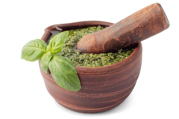 Sauce pesto vert italien dans un mortier d'argile avec pilon isolé sur fond blanc