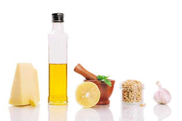 Sauce pesto verte maison au basilic, pignons de pin, ail, citron, huile d'olive et mortier de bois sur fond blanc isolé. ingrédients de la recette sauce italienne pesto dans la composition de la rangée