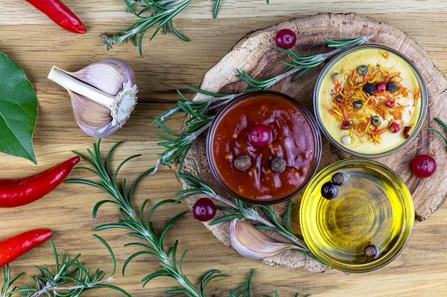 Sauce piquante, moutarde, huile d'olive dans de la vaisselle en verre, épices, branches de romarin sur fond bois.