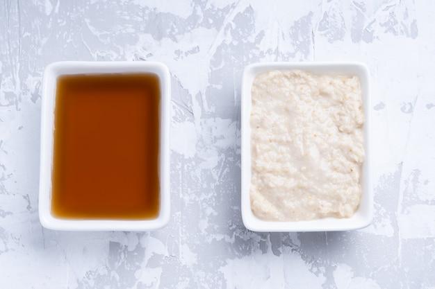 Sauce de poisson dans un bol blanc et sauce blanche sur fond de ciment gris.