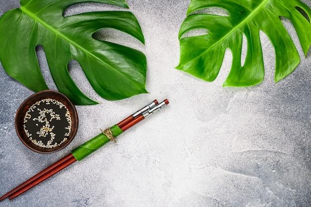 Sauce soja au sésame blanc et baguettes sur une surface de béton grise avec des feuilles tropicales