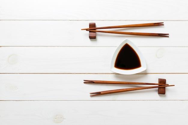 Sauce soja avec des baguettes sur une table en bois blanc