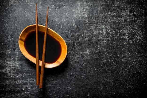 Sauce soja dans un bol avec des baguettes sur table rustique sombre
