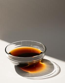 Sauce soja dans une tasse en verre isolé sur fond blanc avec ombre du soleil