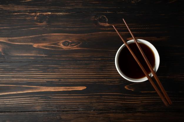 Sauce soja et haricot de soja sur une table en bois.