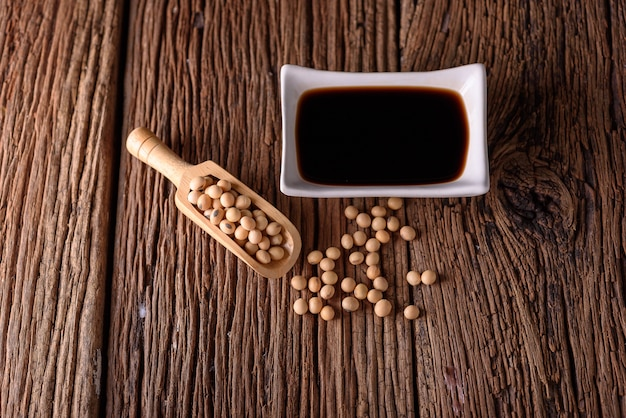 Sauce de soja avec soja sur fond en bois.